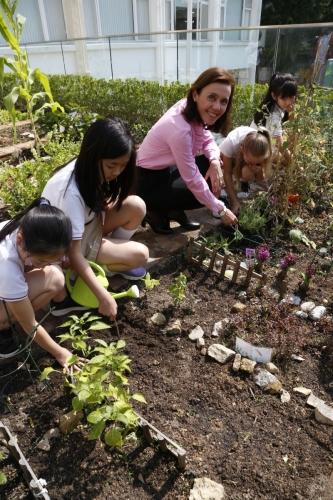 和學生一同經營校園農莊,安白麗樂在其中。