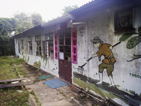 義工在農民屋外牆上畫上田園風光
