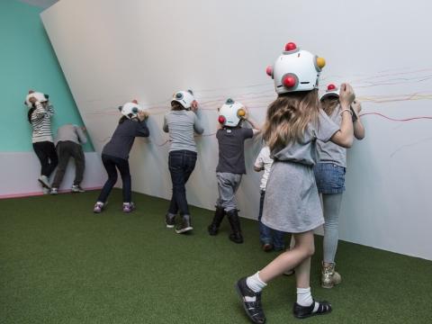 小朋友戴上具有球形蠟筆的「蠟筆頭盔」再用頭搖動來在彎曲的牆上繪畫