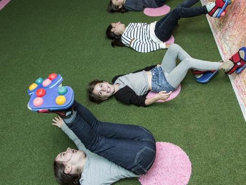 小朋友可穿上特製的「蠟筆鞋」,躺在地上倒轉地用腳滑動繪畫